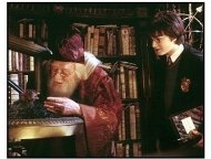"""Harry Potter and the Chamber of Secrets movie still: Harry Potter (Daniel Radcliffe, right) watches as Professor Dumbledore (Richard Harris) feeds Fawkes the Phoenix in """"Harry Potter and the Chamber o"""